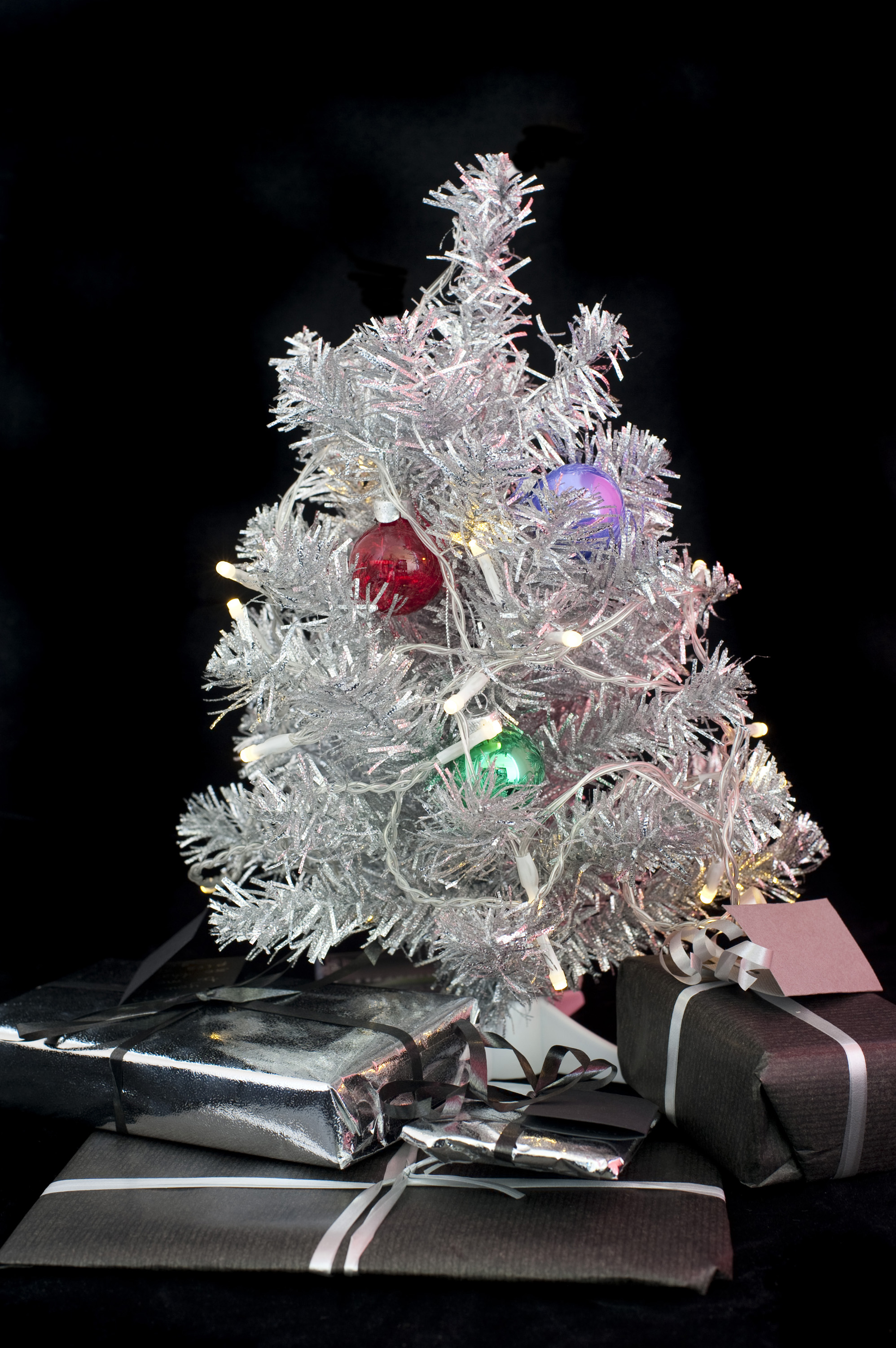 a silver tinsel christmas tree and decorations with gifts beneath