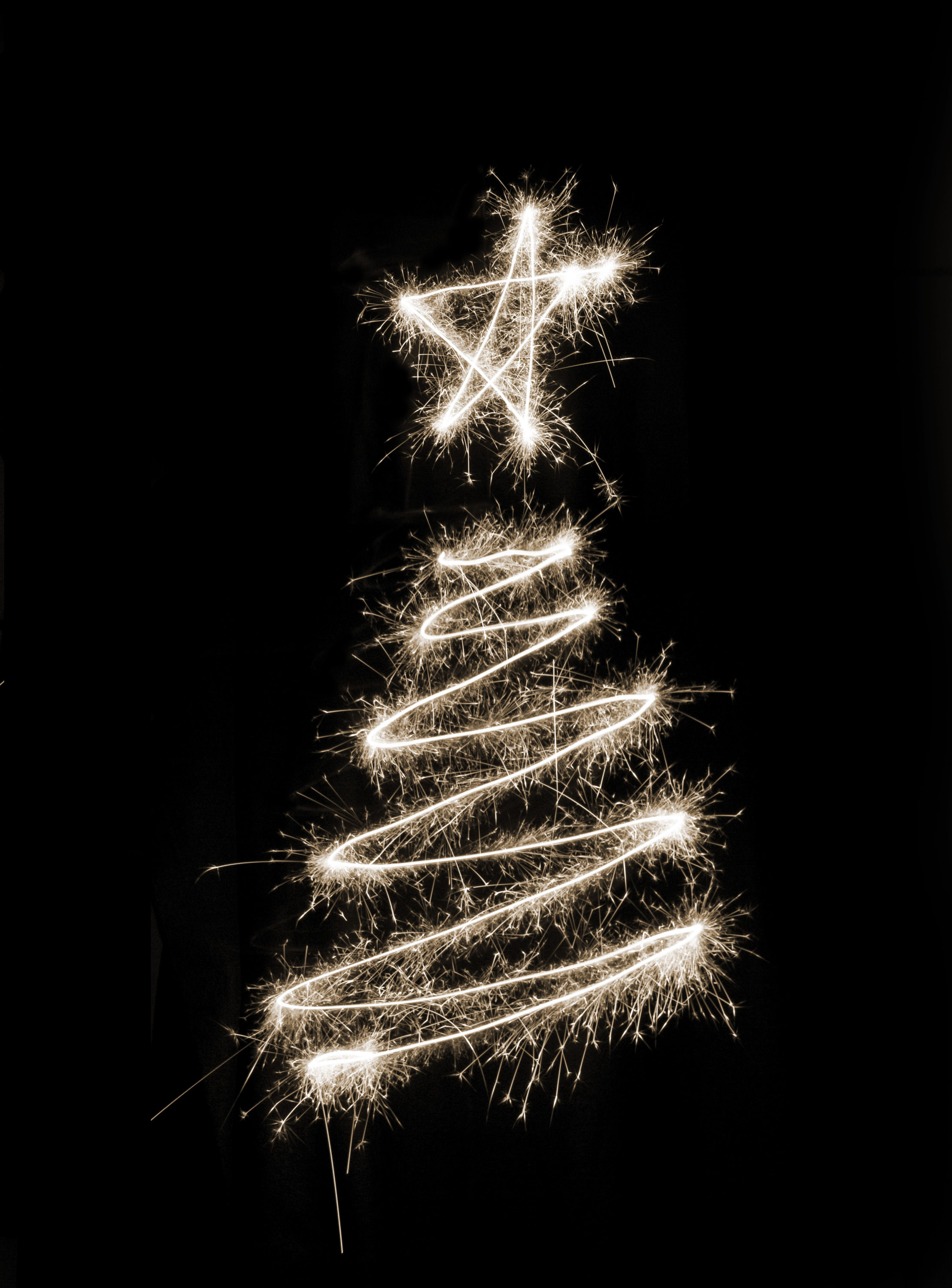 A white christmas tree symbol drawn in sparkler trails