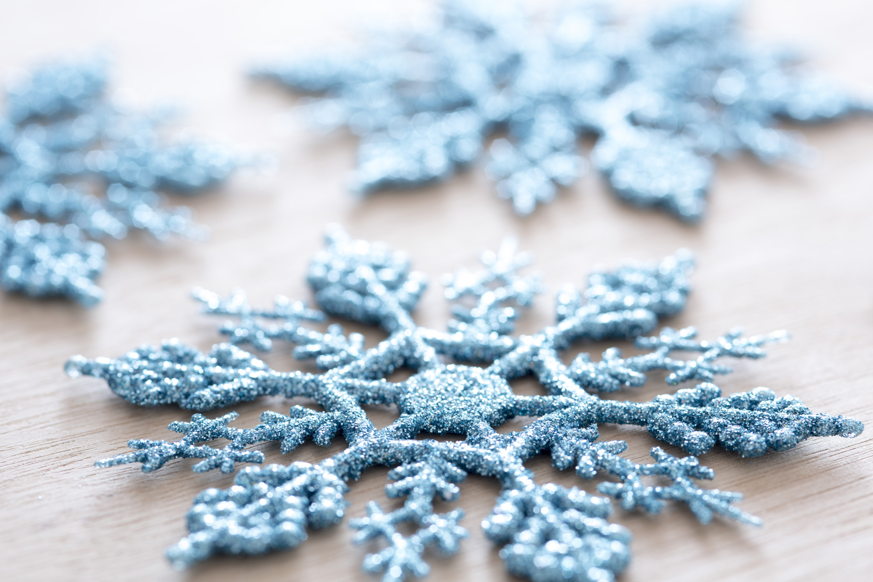 Close up shot of a glittery plastic blue snowflake decoration