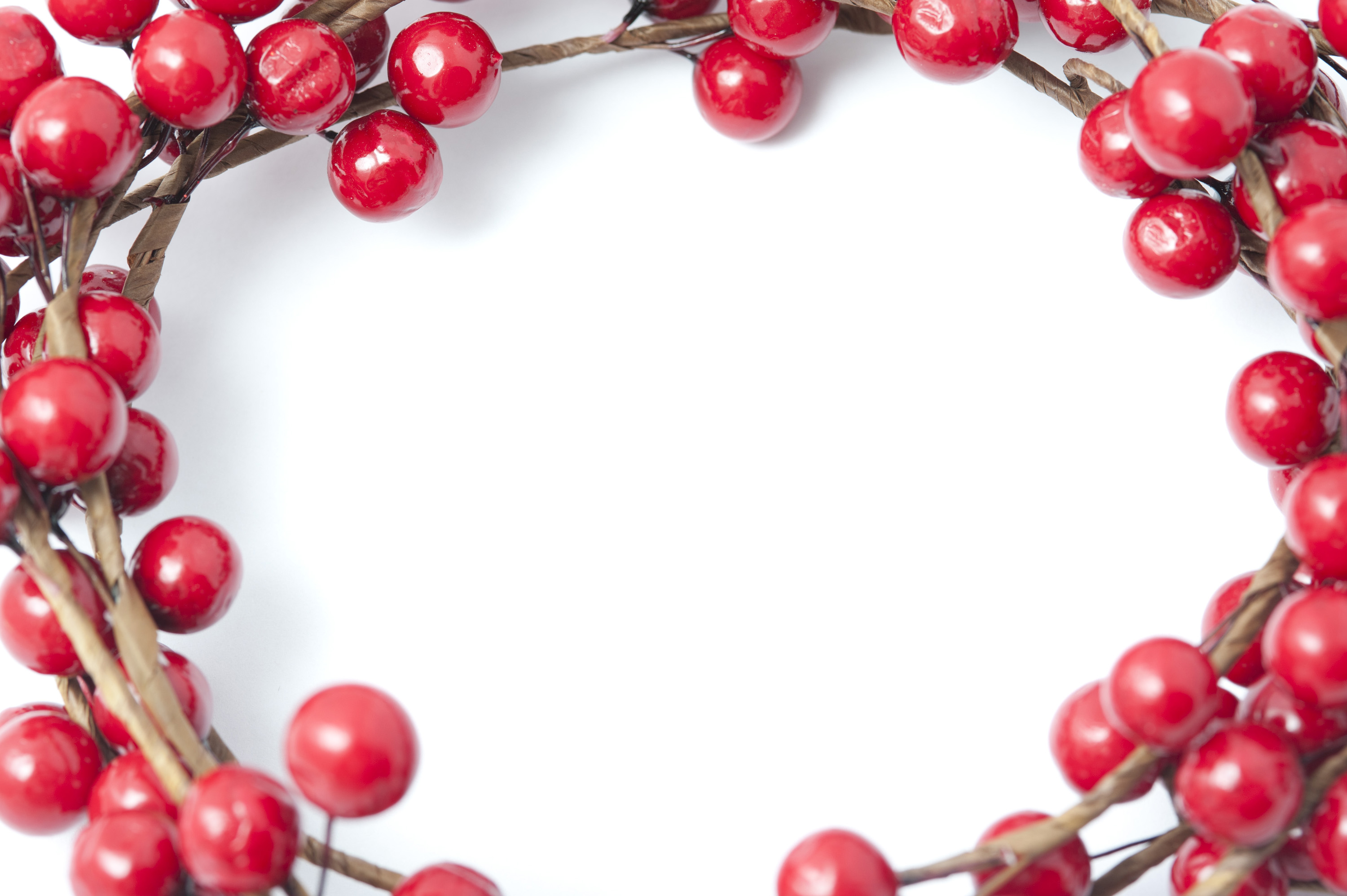 Bright red festive artificial Christmas berry border or frame around central white copy space for your greeting
